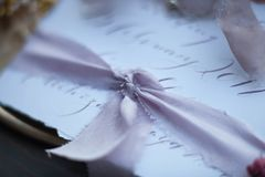 Lilac silk ribbon. Graphic arts of beautiful wedding calligraphy cards with flower and chiffon bobbins on wood background. Beautiful wedding invitation. Details Royalty Free Stock Photos