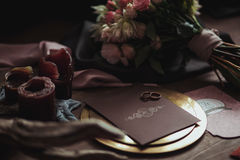 Graphic arts of beautiful wedding pink and brown cards, golden plate with two rings, candles smoke, fabric, bouquet. Snag on wood background. Wedding concept Royalty Free Stock Images