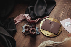 Graphic arts of beautiful wedding pink and brown cards, golden plate with two rings, candles smoke, fabric, snag on wood. Background. Top view. Wedding concept Royalty Free Stock Photos
