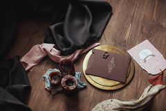 Graphic arts of beautiful wedding pink and brown cards, golden plate with two rings, candles smoke, fabric, snag on wood. Background. Top view. Wedding concept Stock Photos