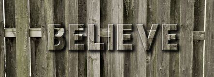 Graphic Background of Text BELIEVE engraved in Wood Fence Royalty Free Stock Image