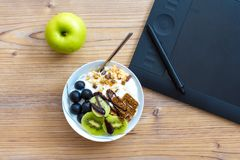 Graphic Design and Healthy Lifestyle Concept with Fruits. Graphic design and healthy lifestyle concept, top view of cup with raw bars and grape, kiwi fruits Stock Images