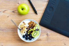 Graphic Design and Healthy Lifestyle Concept with Fruits. Graphic design and healthy lifestyle concept, top view of cup with raw bars and grape, kiwi fruits Stock Photos