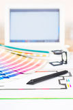 Graphic design and printing concept. Computer with pantone palette, digitizer pen, magnifying lens and printed package scheme, close up with copy space stock images