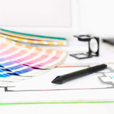 Graphic design and printing concept. Computer with pantone palette, digitizer pen, magnifying lens and printed package scheme, close up with copy space stock image