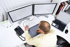 Graphic designer. At work behind two big flatscreen monitors and a laptop A clipping path of the screens is available at the highest resolution royalty free stock image
