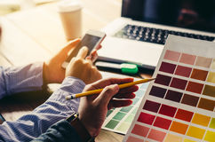 Graphic designer architects who work with laptops. And color comparison tables for design work Royalty Free Stock Images
