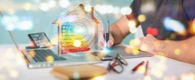 Graphic designer using 3D rendering energy rating chart in a woo. Graphic designer on blurred background using 3D rendering energy rating chart in a wooden house Stock Photos