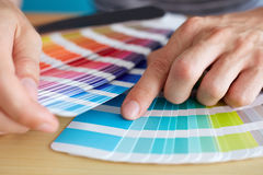 Graphic designer choosing a color. From the palette royalty free stock image