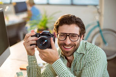 Graphic designer clicking photo from digital camera Royalty Free Stock Image