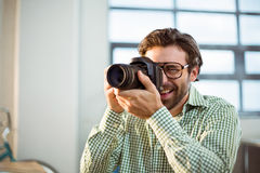 Graphic designer clicking photo from digital camera. In office royalty free stock images