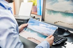 The graphic designer compares the printed photo. With the view on the monitor royalty free stock photography