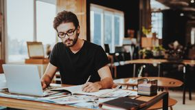 Graphic Designer Concentrated on Work Project. Portrait of Young Bearded Illustrator Sitting at Workplace Looking at Laptop Screen Writting in Notepad Indoors royalty free stock photography