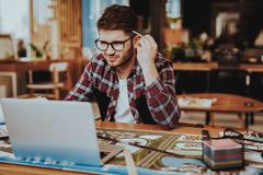 Graphic Designer Concentrated on Work Project. Portrait of Young Bearded Illustrator Wearing Glasses Sitting at Workplace Looking at Laptop Screen Indoors royalty free stock images