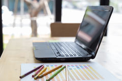 Graphic designer desk table with computer, crayon and color guide palette swatches. Working desk with crayon, color guide palette swatches and laptop computer at royalty free stock images