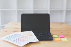 Graphic designer desk table with computer, sticky note and color Stock Photos