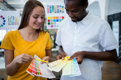 Graphic designer discussing over color swatch with a colleague. In office royalty free stock image