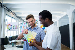 Graphic designer discussing over color swatch with a colleague. In office royalty free stock photo
