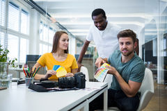 Graphic designer discussing over color swatch with a colleague. In office royalty free stock photography
