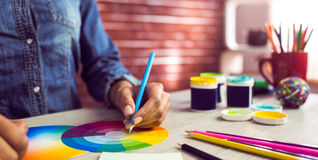 Graphic designer drawing on colour chart. At workplace Stock Photos