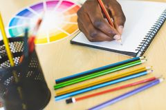 Graphic designer drawing a sketch on notebook art desk. Close-up young African-American graphic designer drawing a sketch on notebook at desk in office royalty free stock photo