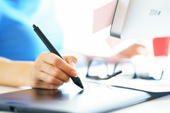Graphic designer drawing something on graphic tablet at the home. Female artist drawing something on graphic tablet at the home office Royalty Free Stock Photography