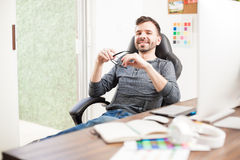 Graphic designer at his office desk. Charming young graphic designer sitting at his office desk while taking a break from work and smiling royalty free stock photo