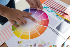 Graphic designer holding color swatch at desk. In the office stock image