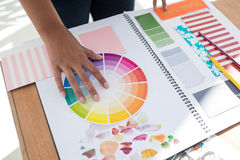 Graphic designer holding color swatch at desk. In the office stock photography