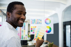Graphic designer holding color swatch. Portrait of graphic designer holding color swatch at his desk in office stock image