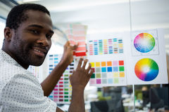 Graphic designer holding color swatch. Portrait of graphic designer holding color swatch at his desk in office stock photography