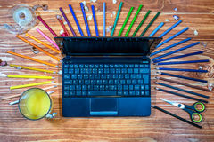 Graphic designer with laptop and color palette. Graphic designer with laptop and color pencils on a wooden table royalty free stock photos
