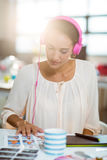 Graphic designer listening to music and looking at color swatch. In office royalty free stock photography