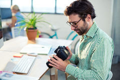 Graphic designer looking at pictures in digital camera Royalty Free Stock Photo