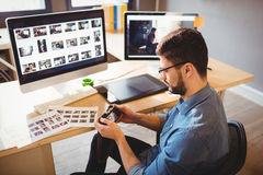 Graphic designer looking at pictures in digital camera Stock Images