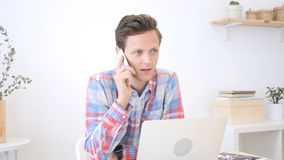 Graphic Designer , man phoning with his mobile , creative office stock photo