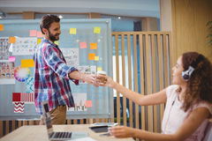 Graphic designer offering coffee to his colleague. In office royalty free stock photography