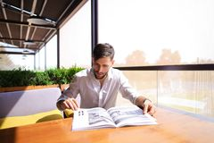 Graphic designer reading catalog at cafe. Young graphic designer watching catalog at cafe at table. Handsome man in white classic style shirt has beard and royalty free stock photos