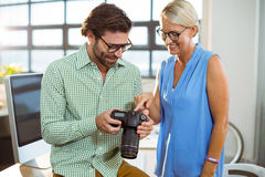 Graphic designer showing photo to colleague on digital camera Royalty Free Stock Images