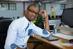 Graphic designer sitting at desk. Portrait of graphic designer sitting at desk in office royalty free stock images