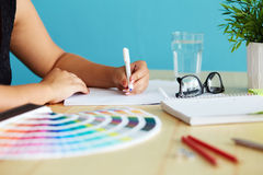 Graphic designer. At sketching the design stock photo