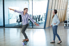 Graphic designer standing on hoverboard. Graphic designer standing on hover board in office Stock Photo