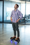 Graphic designer standing on hoverboard in office. Graphic designer standing with hand on hip on hoverboard in office Stock Photography