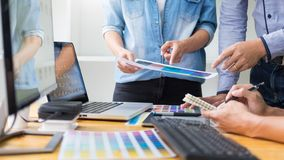 Graphic designer team working on web design using color swatches editing artwork using tablet and a stylus At Desks In Busy stock image