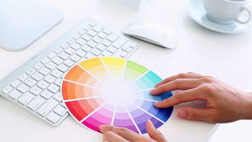 Graphic designer using colour wheel at his desk stock video footage