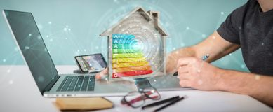 Graphic designer using 3D rendering energy rating chart in a woo. Graphic designer on blurred background using 3D rendering energy rating chart in a wooden house Stock Photo