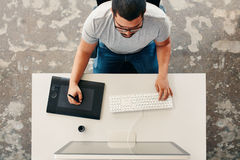 Graphic designer using digital graphics tablet and desktop. Top view of a male graphic designer using digital graphics tablet and desktop in the office. Editor Stock Photos