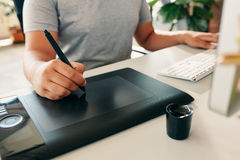 Graphic designer using digital graphics tablet and desktop Stock Photos