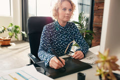 Graphic designer using digital graphics tablet and desktop Stock Photography