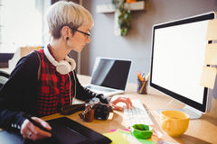 Graphic designer using graphics tablet. Female graphic designer using graphic tablet while working on computer at office Stock Photos
